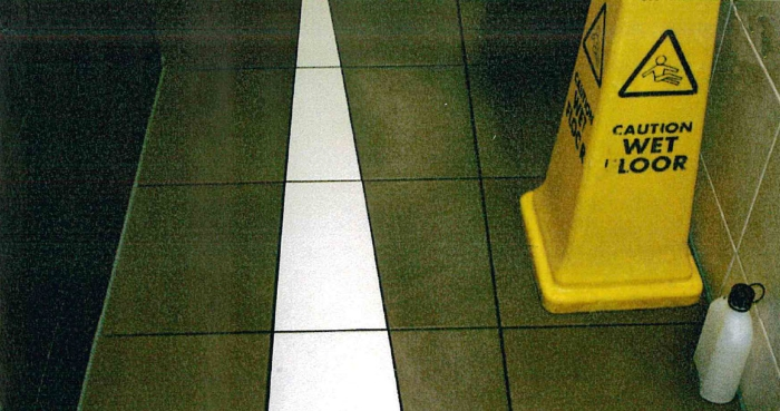Wet Floor sign on tiled floor in retail premises